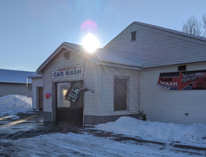 Depicts car wash with sun shining and open sign